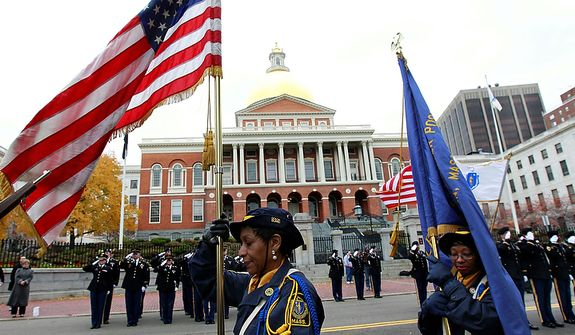 A member of an American Legion color guard (center) carries an American flag during Veterans Day ceremonies in front of the Massachusetts Statehouse in Boston on Friday, Nov. 11, 2011. (AP Photo/Steven Senne)