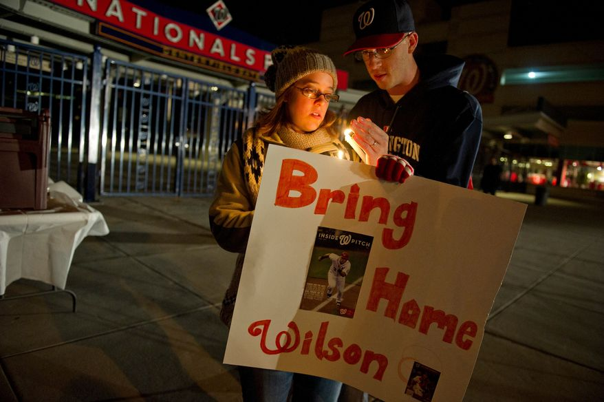 Kirsten Irwin and her husband Steve, of Washington D.C., work to keep their candles lit in the wind during a candlelight vigil for Nationals' rookie catcher Wilson Ramos at Nationals Park in Washington, DC, Friday, November 11, 2011. Ramos was kidnapped by armed gunmen in front of his family home in Venezuela on Wednesday night. (Rod Lamkey Jr. / The Washington Times)