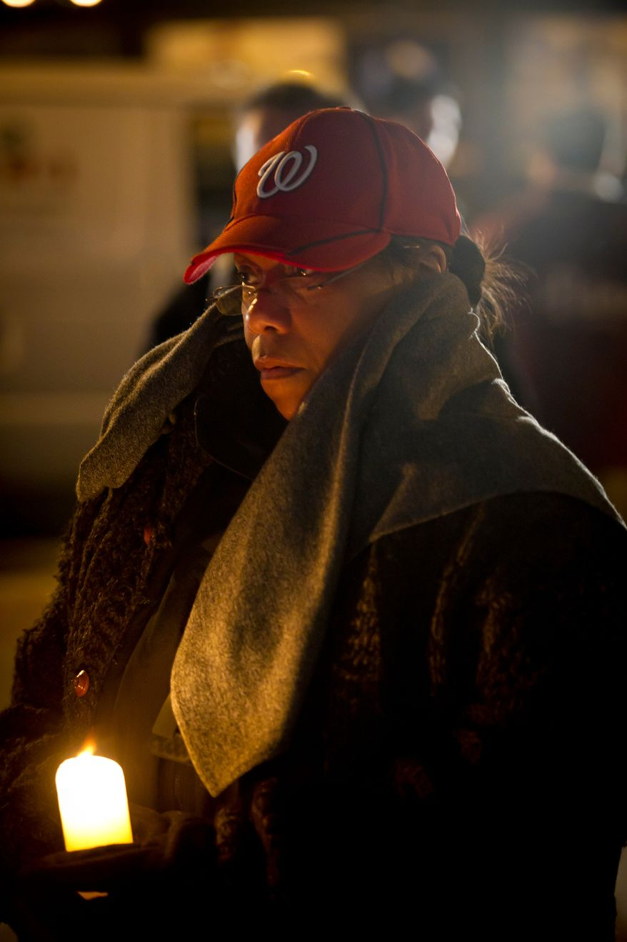 Lauretta Rosado, of Vienna, Va, is bundled up against the cold as she joins other fans for a candlelight vigil for Nationals' rookie catcher Wilson Ramos at Nationals Park in Washington, DC, Friday, November 11, 2011. Ramos was kidnapped by armed gunmen in front of his family home in Venezuela on Wednesday night. (Rod Lamkey Jr. / The Washington Times)