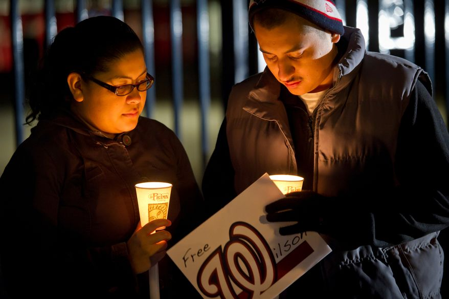 Claudia Alvarez and her boyfriend Ebiel Barbosa both of Washington D.C., keep their candles lit against the wind during a candlelight vigil for Nationals' rookie catcher Wilson Ramos at Nationals Park in Washington, DC, Friday, November 11, 2011. Ramos was kidnapped by armed gunmen in front of his family home in Venezuela on Wednesday night. (Rod Lamkey Jr. / The Washington Times)