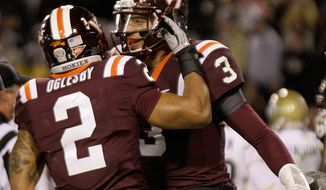 Virginia Tech quarterback Logan Thomas (3) celebrates with teammate Josh Oglesby (2) after scoring a touchdown in the third quarter of an NCAA college football game, Thursday, Nov. 10, 2011 in Atlanta. Virginia Tech won 37-26. (AP Photo/David Goldman)