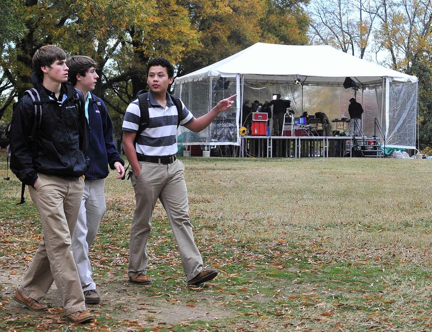 Wofford College Freshmen, from left to right, Charles Johnson, Corey Holcomb and Bradley Lara walk by a CBS anchor remote location located behind the Wofford College main building in Spartanburg, S.C., on Thursday, Nov. 10, 2011, as CBS crews prepare for the Republican presidential debate that will held Saturday, Nov. 12, 2011, at 8 p.m. (AP Photo/Spartanburg Herald-Journal/Michael Justus)