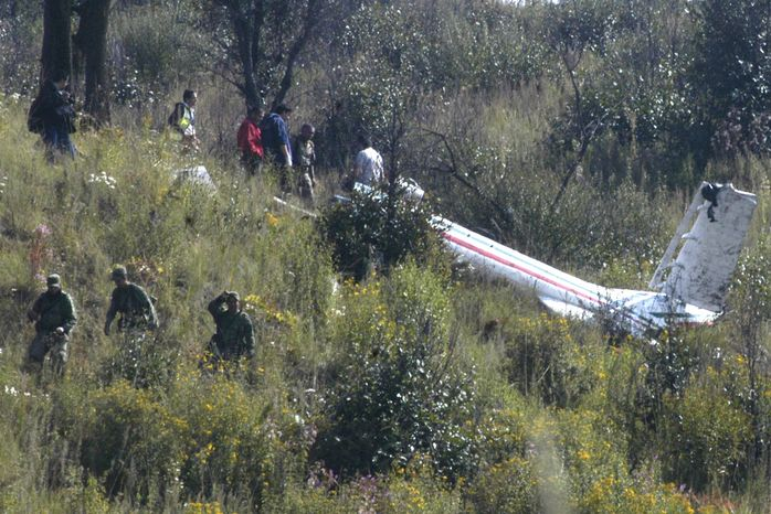Soldiers and investigators examine the wreckage of a helicopter that was carrying Mexico's Interior Minister Francisco Blake Mora, at a mountainous area in Santa Catarina Ayatzingo, southeast of Mexico City, Friday, Nov. 11, 2011. (AP Photo)