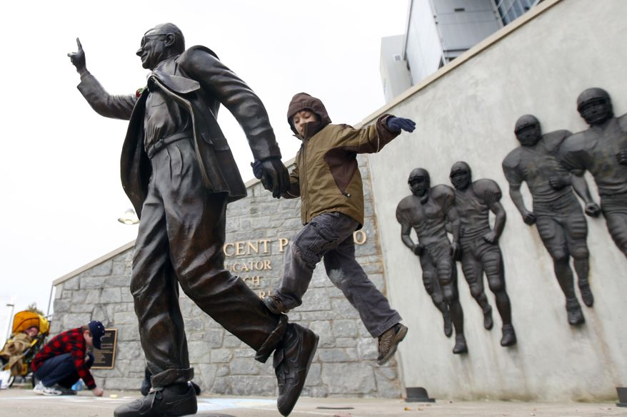Merrick Briggs, 6, climbs on a statue of Joe Paterno outside Beaver Stadium on Penn State's campus, Friday, Nov. 11, 2011, in State College, Pa. On Wednesday, Penn State Board of Trustees fired football coach Joe Paterno and university President Graham Spanier amid child sex abuse allegations against an assistant coach. (AP Photo/Matt Rourke)