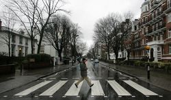 """The Beatles were photographed on this street crossing for the band's """"Abbey Road"""" album cover. It's outside Abbey Road Studios (left) in London. EMI Group Ltd., the recording and publishing home of the Beatles, is being sold in two parts for $4.1 billion. (Associated Press)"""