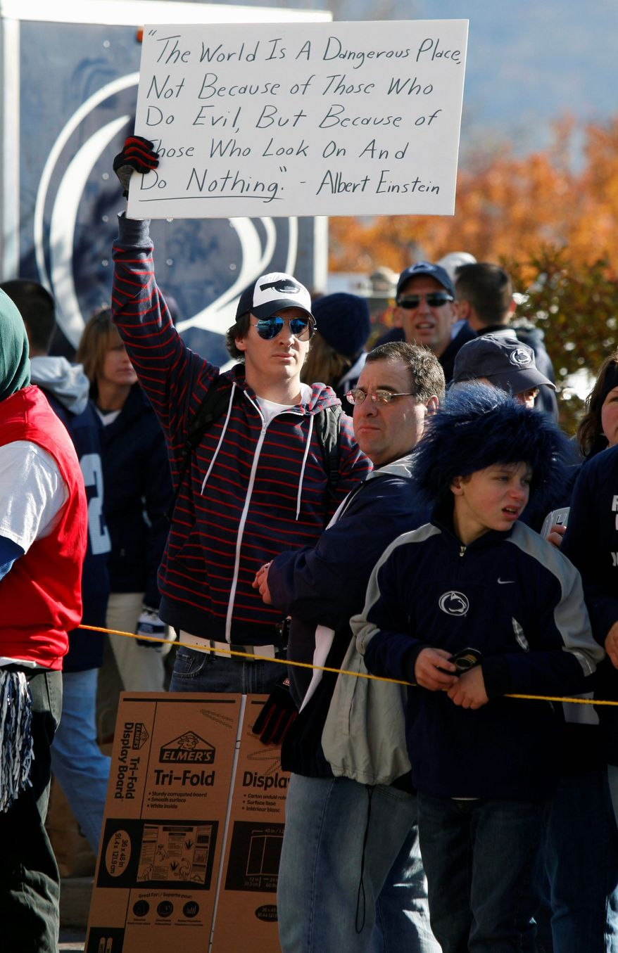 A fan holds a sign before the team's arrival at Penn State's Beaver Stadium before their game with the University of Nebraska Saturday, Nov. 12, 2011 in State College, Pa. Penn State played for the first time in decades without former head coach Joe Paterno, after he was fired in the wake of a child sex abuse scandal involving a former assistant coach. (AP Photo/Alex Brandon)