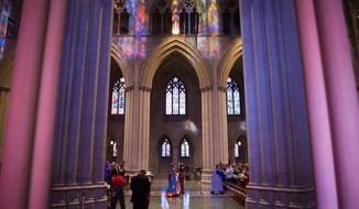 The Rev. Mariann Edgar Budde (center) walks through the Washington National Cathedral. She asked those who attended the first service at the cathedral since an August earthquake to see the ongoing recovery as a time to strengthen and rebuild. (Andrew Harnik/The Washington Times)