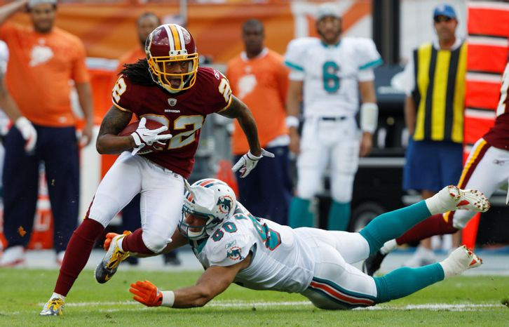 Washington Redskins defensive back Kevin Barnes (22) dashes around Miami Dolphins tight end Anthony Fasano (80) after Barnes intercepted a p