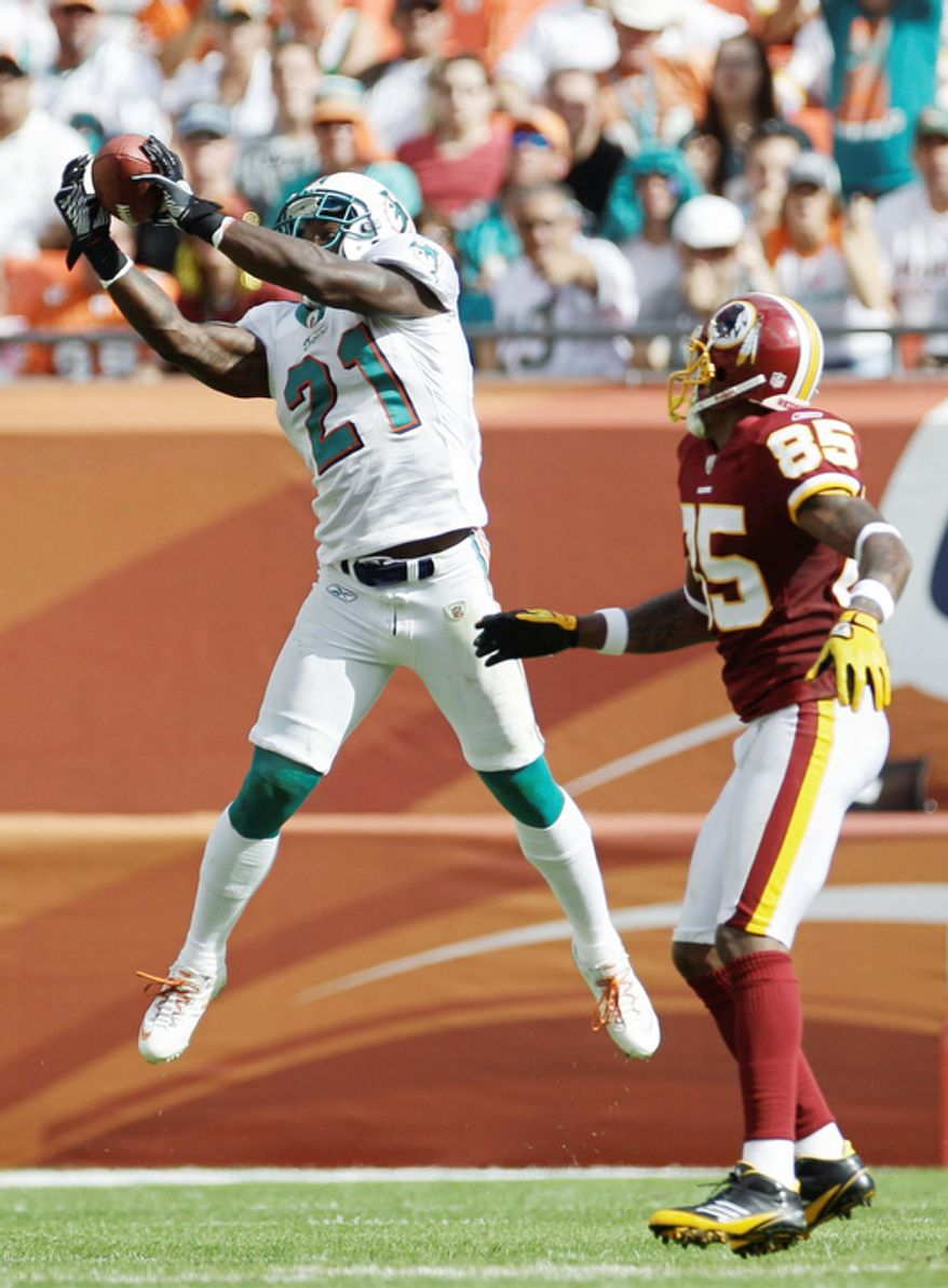 Miami Dolphins cornerback Vontae Davis (21) intercepts a pass as Washington Redskins wide receiver Leonard Hankerson (85) looks on during the second quarter. (AP Photo/J Pat Carter)