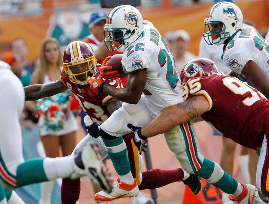 Miami Dolphins running back Reggie Bush (22) runs for a touchdown as Washington Redskins cornerback DeAngelo Hall, left, and Washington Redskins nose tackle Chris Neild (95) defend during the fourth quarter. (AP Photo/Hans Deryk)
