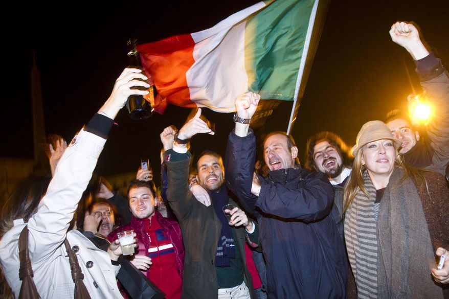 People celebrate with an Italian flag in Rome on Nov. 12, 2011, after Premier Silvio Berlusconi resigned. (Associated Press)