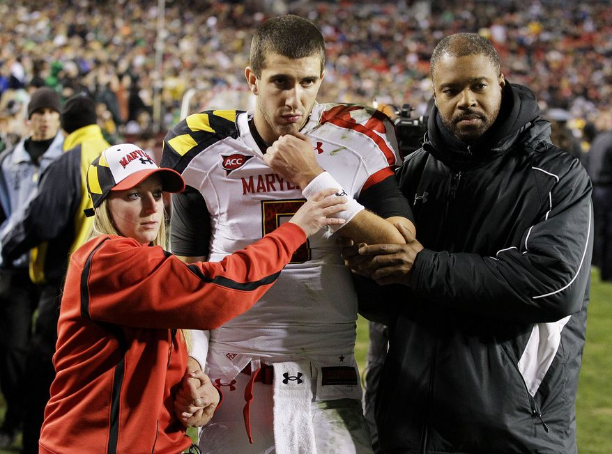 Maryland quarterback Danny O'Brien is assisted off the field after breaking a bone in his left arm during a play in the second half against Notre Dame in Landover, Md., Saturday, Nov. 12, 2011. O'Brien will miss the rest of the season. (AP Photo/Patrick Semansky)