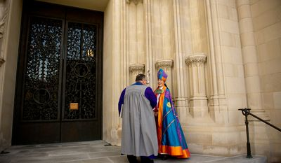 The Reverend Dr. Mariann Edgar Buddle shares a laugh outside with Verger Duke DuTeil before she is consecrated as the ninth bishop of Washington. (Andrew Harnik / The Washington Times)