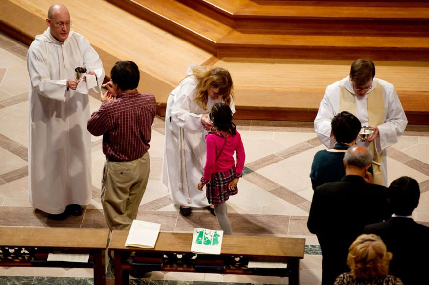 A young churchgoer receives communion, center, at National Cathedral before the Service of Holy Eucharist begins. (Andrew Harnik / The Washington Times)