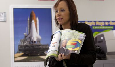 Michelle Hartman works with her elementary students at a Plantation, Fla. school. Teachers, who have historically been paid less than other professionals, have long found themselves taking second jobs. The high numbers raise long simmering questions about elevating the teaching status in the United States, and what the impact is for students in the classroom. (AP Photo/J Pat Carter)