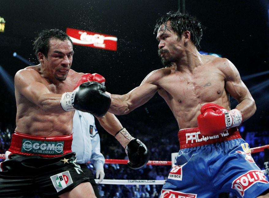 Manny Pacquiao (right) hits Juan Manuel Marquez during their WBO welterweight title fight on Nov. 12, 2011, in Las Vegas. (Associated Press)