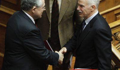 Greek Prime Minister Lucas Papademos, left, is congratulated by former Premier socialist leader George Papandreou after his speech at Greek Parliament in Athens, Monday, Nov. 14, 2011. (AP Photo/Thanassis Stavrakis)