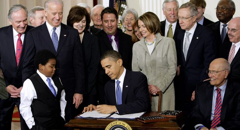 ** FILE ** President Obama signs the health care bill at the White House in Washington on March 23, 2010, flanked by smiling supporters from the House and Senate as well as Victoria Reggie Kennedy (behind Mr. Obama's right shoulder), widow of Sen. Edward M. Kennedy, who was a champion of the legislation. (Associated Press)