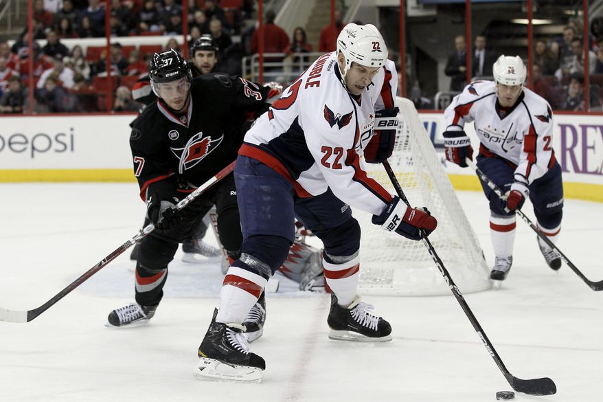 Washington Capitals' Mike Knuble (22) controls the puck against Carolina Hurricanes' Tim Brent (37) during the first period of an NHL game in Raleigh, N.C., Friday, Nov. 4, 2011. (AP Photo/Gerry Broome)