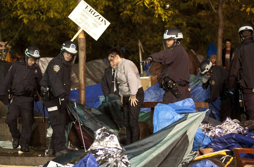 Police officers order Occupy Wall Street protesters to leave Zuccotti Park, their longtime encampment in New York, early Tuesday, Nov. 15, 2011. Protesters were told they could return, but without sleeping bags, tarps or tents. (AP Photo/John Minchillo)