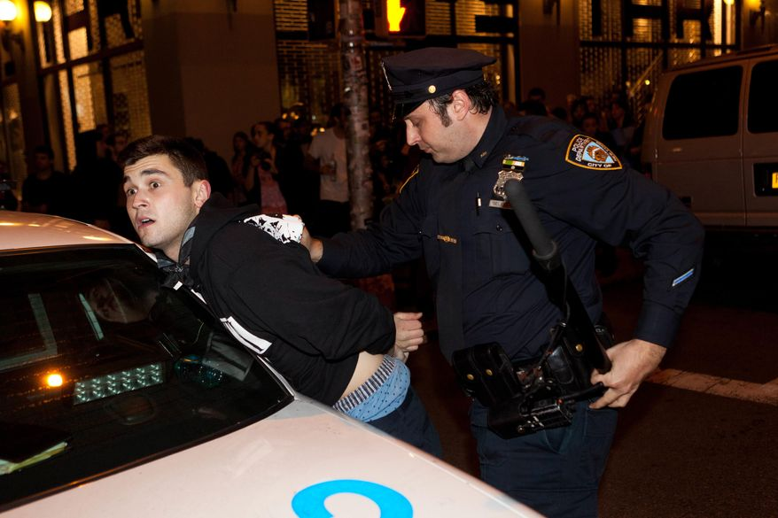 An Occupy Wall Street protester is arrested during a march on Broadway, Tuesday, Nov. 15, 2011, in New York, after police ordered demonstrators to leave their encampment in Zuccotti Park. (AP Photo/John Minchillo)