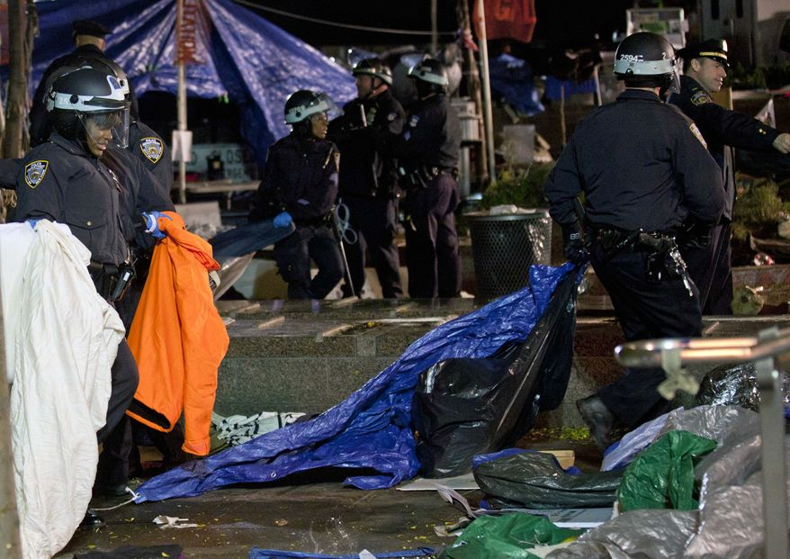 Police officers clean up the Occupy Wall Street encampment at Zuccotti Park in New York after ordering protesters to leave, early Tuesday, Nov. 15, 2011. (AP Photo/John Minchillo)