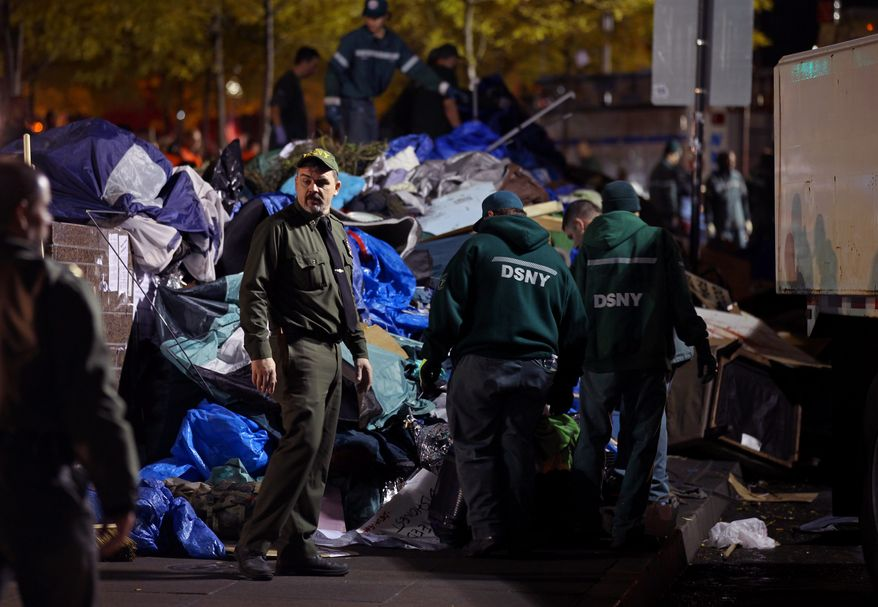 Sanitation workers pile debris from the Occupy Wall Street encampment at Zuccotti Park in New York on Tuesday, Nov. 15, 2011, after police ordered protesters to leave. (AP Photo/Craig Ruttle)