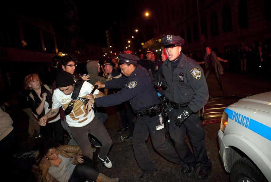Occupy Wall Street protesters clash with police near Zuccotti Park after being ordered to leave their longtime encampment in New York, early Tuesday, Nov. 15, 2011. At about 1 a.m. Tuesday, police handed out notices from the park's owner, Brookfield Office Properties, and the city saying that the park had to be cleared because it had become unsanitary and hazardous. Protesters were told they could return, but without sleeping bags, tarps or tents. (AP Photo/John Minchillo)