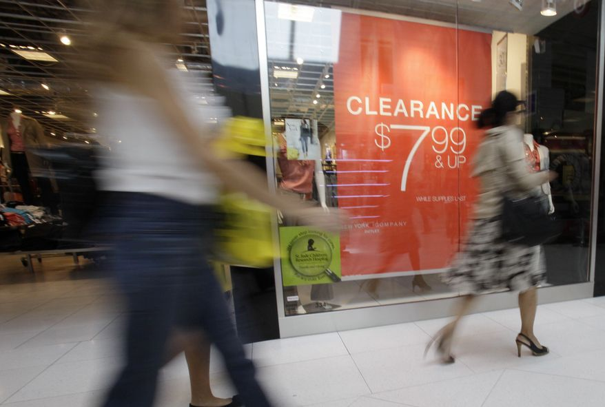 Shoppers walk past a clearance sign at the New York & Company outlet store Nov. 9, 2011, at the Dolphin Mall in Miami. Americans spent more on autos, electronics and building supplies in October, pushing retail sales up for a fifth straight month. (Associated Press)