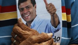 **FILE** A campaign flier with an image of opposition leader Leopoldo Lopez is held Sept. 24, 2011, by a supporter during a campaign rally where Lopez launched his presidential bid in Caracas, Venezuela. (Associated Press)