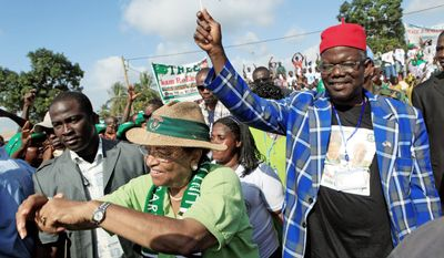 Liberian President Ellen Johnson-Sirleaf (below center) walks with Prince Johnson (below right) at a rally in Monrovia, Liberia, on Nov. 6 before the presidential election two days later. Mrs. Johnson-Sirleaf won re-election and denies making concessions to Mr. Johnson, an ex-warlord linked to atrocities. (Associated Press)