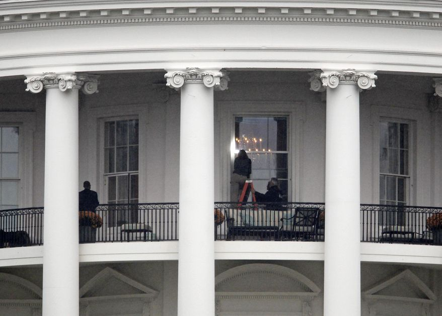 Law enforcement officers photograph a window at the White House on Nov. 16, 2011, after two bullets were found the previous day on the property. A bullet hit an exterior window of the White House and was stopped by ballistic glass, the Secret Service said. An additional round of ammunition was found on the White House exterior. (Associated Press)