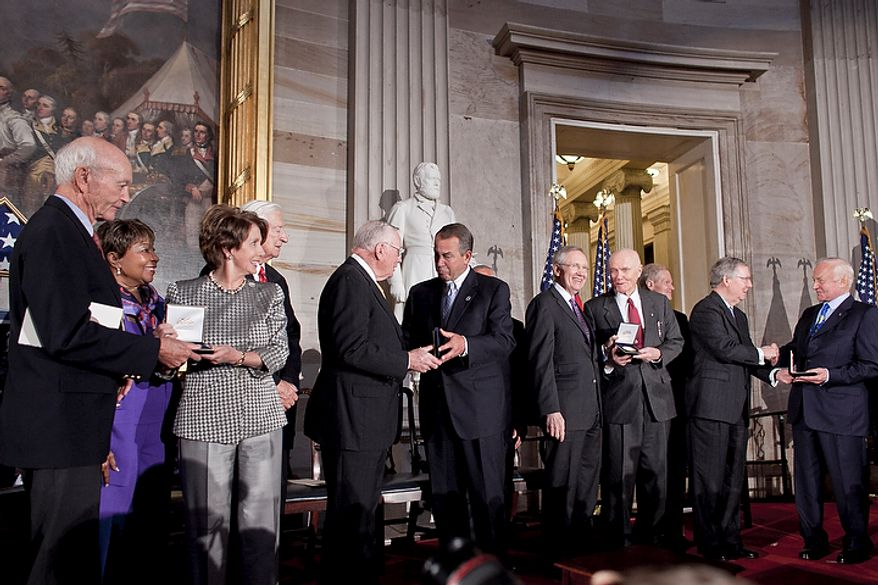 Astronaut Michael Collins (left) receives a Congressional Gold Medal from House Minority Leader Nancy Pelosi, California Democrat, as fellow astronaut Neil Armstrong (fifth from left) receives his medal from House Speaker John Boehner, Ohio Republican, Senate Majority Leader Harry Reid (fifth from right), Nevada Democrat, presents to astronaut John Glenn, and Senate Minority Leader Mitch McConnell (second from right), Kentucky Republican, to Buzz Aldrin during a Congressional Gold Medal ceremony at the Capitol building in Washington on Nov. 16, 2011. (T.J. Kirkpatrick/The Washington Times)
