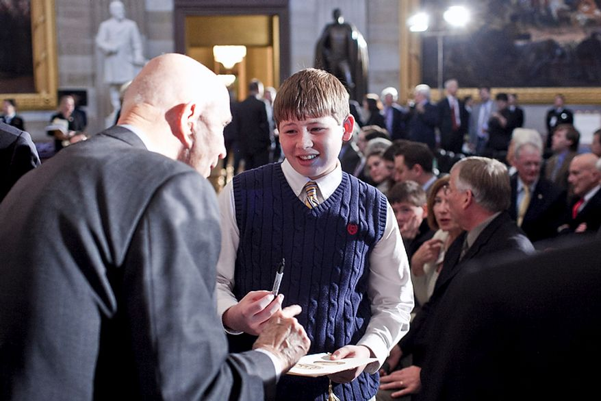 J.D. Kelly (center), 12, of Lexington Park, Md., asks for an autograph from Gen. Tom Stafford, a NASA astronaut who flew in two Gemini space flights and commanded Apollo 10 and the Apollo-Soyuz flight, during a Congressional Gold Medal ceremony in honor of astronauts Michael Collins, Neil Armstrong, John Glenn and Buzz Aldrin at the Capitol building in Washington on Nov. 16, 2011. (T.J. Kirkpatrick/The Washington Times)