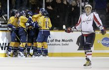 Washington Capitals left wing Alex Ovechkin, right, looks up at the scoreboard as Nashville Predators players celebrate a goal by Martin Erat in the third period of an NHL game Tuesday, Nov. 15, 2011, in Nashville, Tenn. The Predators won 3-1. (AP Photo/Mark Humphrey)