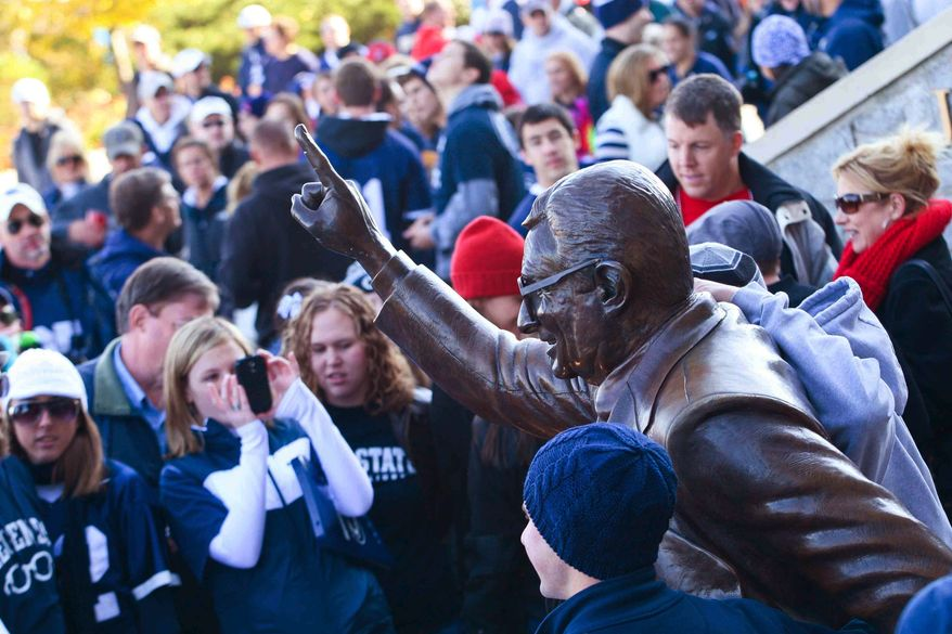 Penn State fans gather outside Beaver Stadium to get a picture next to Joe Paterno's statue before the game between Penn State and Nebraska Saturday, Nov. 12, 2011 in State College, Pa. (AP Photo/The Wilmington News-Journal, Suchat Pederson)