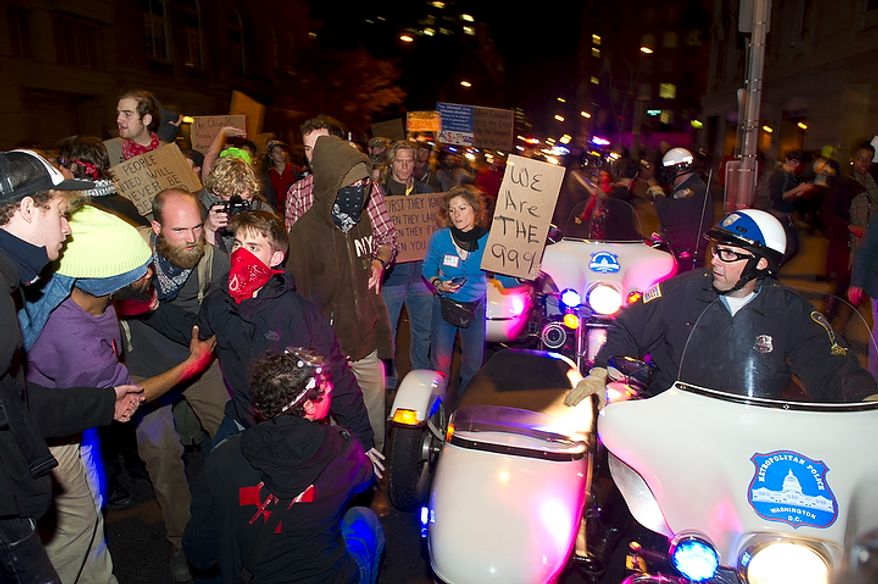 A protester is helped up from the street after being bumped by a police officer on his motorcycle during an Occupy D.C. march through the streets of downtown Washington, D.C., Tuesday, Nov. 15, 2011,  to show support for the Occupy Wall Street movement. (Rod Lamkey Jr./The Washington Times)