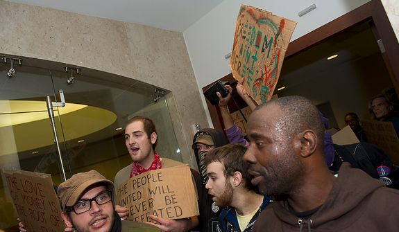 Demonstrators with Occupy D.C. occupy the lobby of the Victor Building in downtown Washington, D.C., Tuesday, Nov. 15, 2011, to show support for the Occupy Wall Street movement. (Rod Lamkey Jr./The Washington Times)