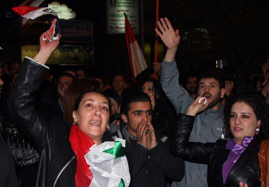Pro-Syrian regime protesters shout slogans against the Arab League as a woman throws an egg during a protest in front of the embassy of Qatar, in Damascus, Syria, on Saturday Nov. 12, 2011. (AP Photo/Bassem Tellawi)