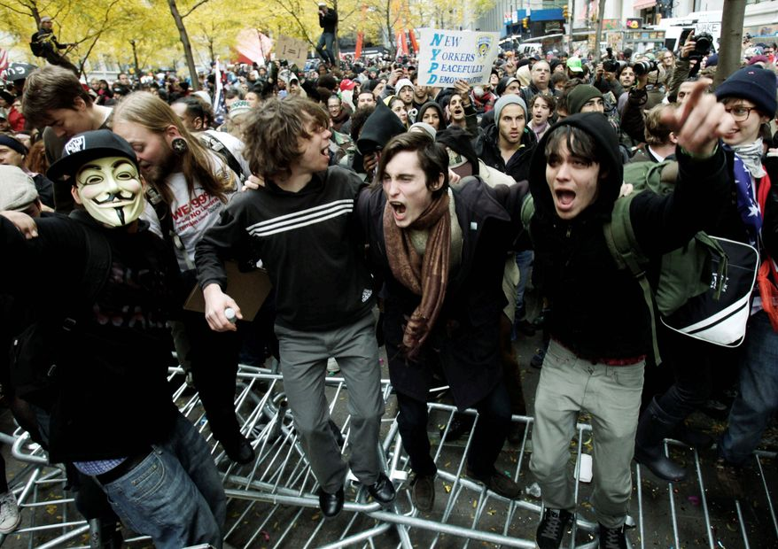Protesters jump on police barricades on Thursday, Nov. 17, 2011, in New York's Zuccotti Park, where the Occupy Wall Street movement began two months earlier. Demonstrators from coast to coast joined their call for economic justice. (Associated Press)