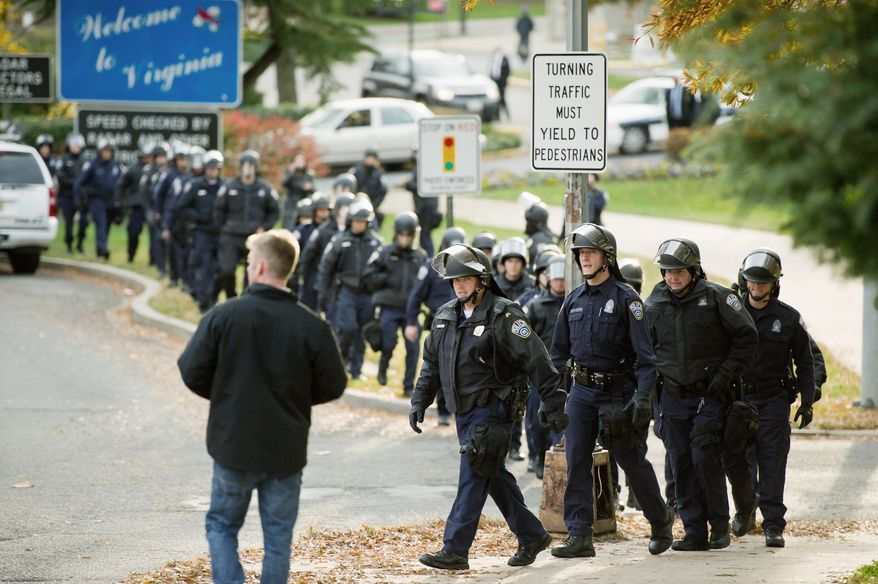 Arlington County Police officers in riot helmets take their position on the Virginia side of the Francis Scott Key Bridge. There were no reports of arrests or injuries as Occupy D.C. protesters marched from McPherson Square to the bridge. (Andrew Harnik/The Washington Times)