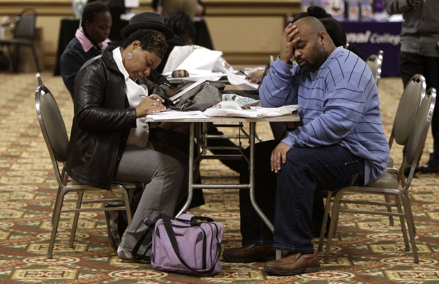 Tonya Crenshaw, left, and Kendrick Haraalson fill out applications at a job fair Wednesday, Oct. 26, 2011, in Brookpark, Ohio. The number of people seeking unemployment benefits dipped slightly last week, though not by enough to suggest that hiring is picking up. (AP Photo/Tony Dejak)
