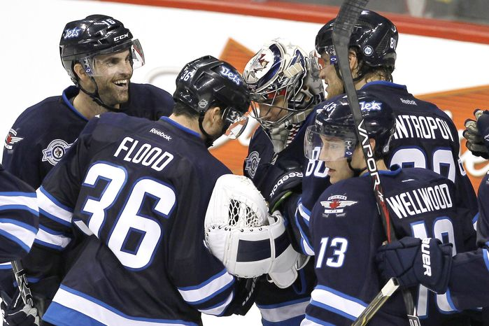 Winnipeg Jets teammates congratulate goalie Ondrej Pavelec after the Jets defeated the Tampa Bay Lightning 5-2 Monday, Nov. 14, 2011, in Winnipeg, Manitoba. (AP Photo/The Canadian Press, John Woods)