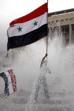 A pro-Syrian regime protester waves a Syrian flag from a fountain during a demonstration in Damascus, Syria, on Nov. 16, 2011, to protest against the Arab League meeting being held in Morocco. (Associated Press)