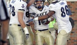 Navy running back Mike Stukel (17) is congratulated by teammates after scoring their final touchdown in the fourth quarter against SMU, Saturday, Nov. 12, 2011, at Gerald J. Ford Stadium in Dallas, Texas. Navy won the game 24-17. (AP Photo/John F. Rhodes)