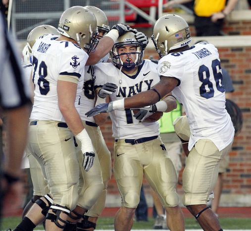 Navy running back Mike Stukel (17) is congratulated by teammates after scoring their final touchdown in the fourth quarter against SMU, Saturday, Nov. 12, 2011, at Gerald J. Ford Stadium in Dallas, Texas. Navy won the game