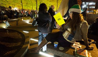 Lauren Belski, 31, of Brooklyn reads in a newly tent-free Zuccotti Park during the early morning hours, Wednesday, Nov. 16, 2011, in New York. (AP Photo/John Minchillo)