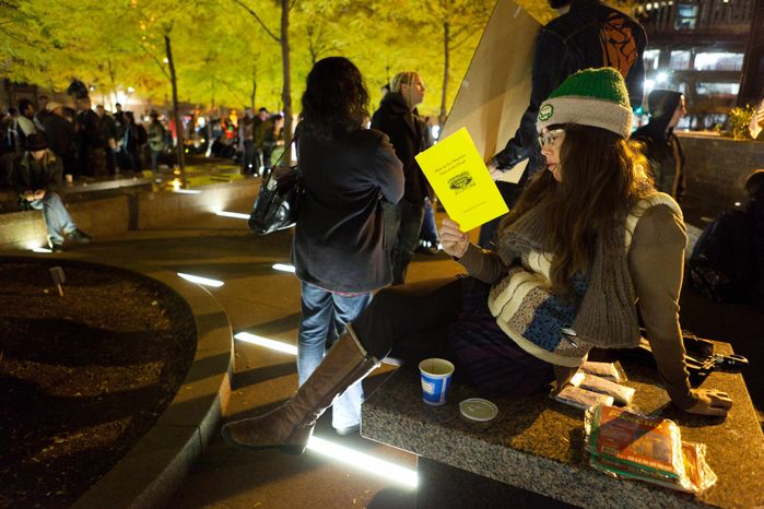 Lauren Belski, 31, of Brooklyn reads in a newly tent-free Zuccotti Park during the early morning hours, Wednesday, Nov. 16, 2011, in New York. (