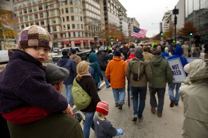 A young child looks around as Occupy DC protesters march from McPherson Square down K Street to the Key Bridge which connects Georgetown to Northern Virginia, Washington, DC, Thursday, November 17, 2011. (Andrew Harnik/The Washington Times)