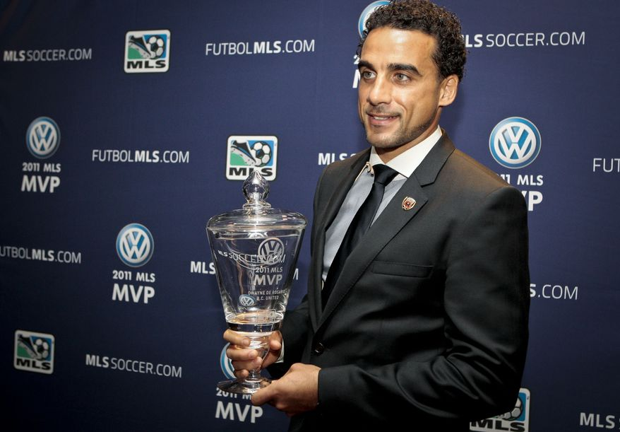 ** FILE ** D.C. United midfielder Dwayne De Rosario holds the MLS Most Vaulable Player trophy during a news conference on Friday, Nov. 18, 2011, in Carson, Calif. (AP Photo/Bret Hartman)